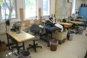 shows sewing room where all smoke jumpers must examine parachutes and make repairs using sewing machines.